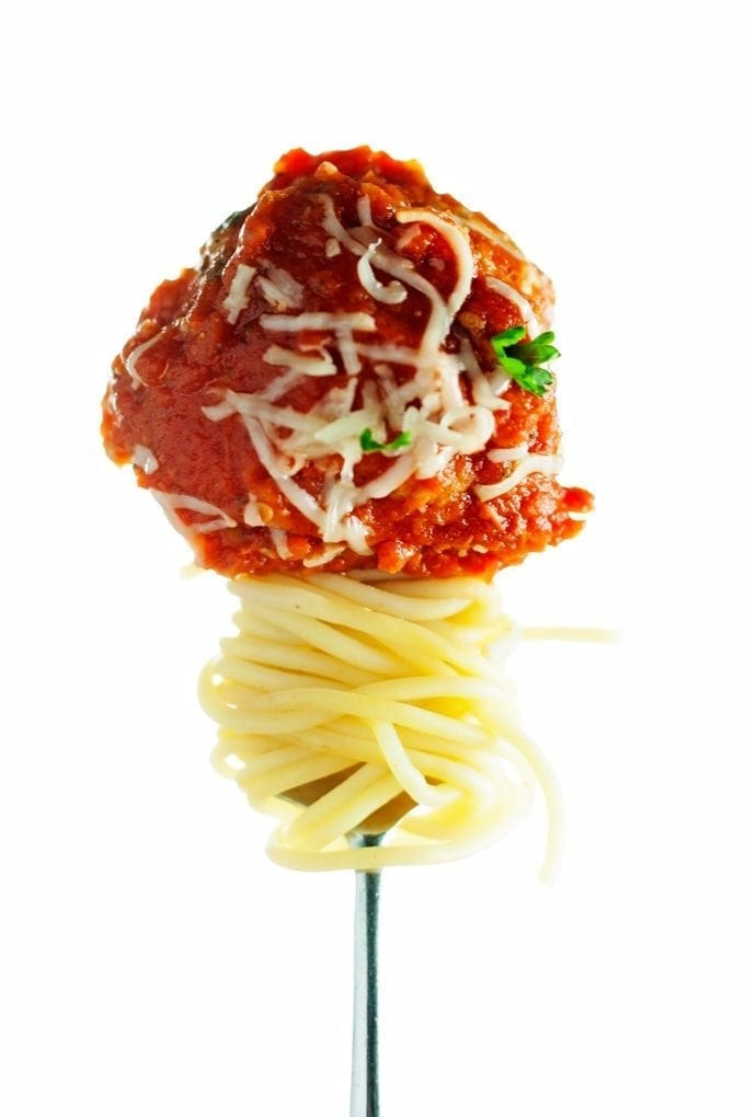 baked turkey meatball displayed on a fork with spaghetti