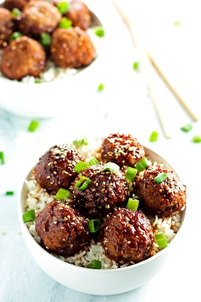 Two bowls overflowing with beef teriyaki meatballs. Served over rice and topped with sesame seeds and green onions.