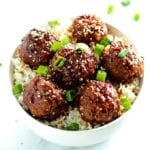beef teriyaki meatballs served over rice and topped with sesame seeds and green onions