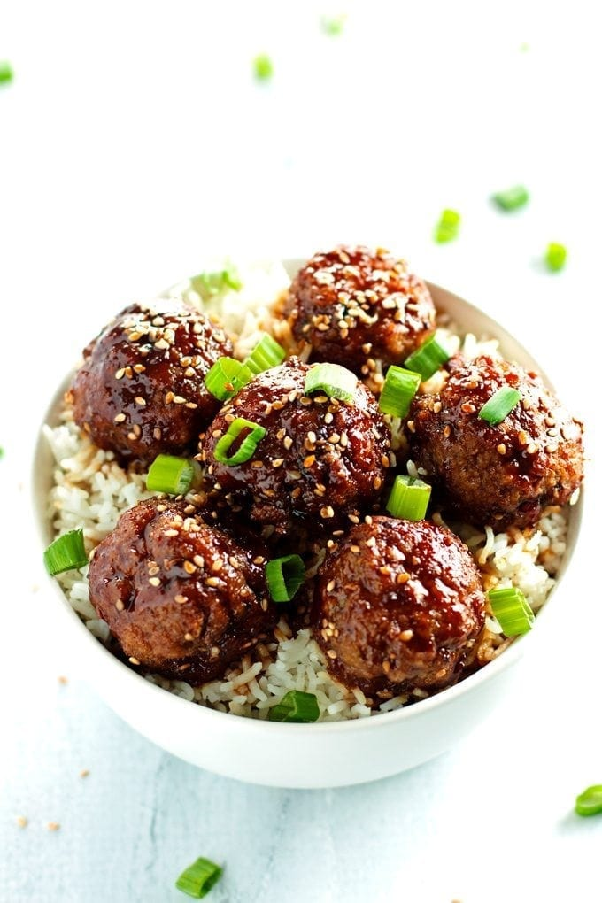 a bowl full of beef teriyaki meatballs served over rice and topped with green onions and sesame seeds.