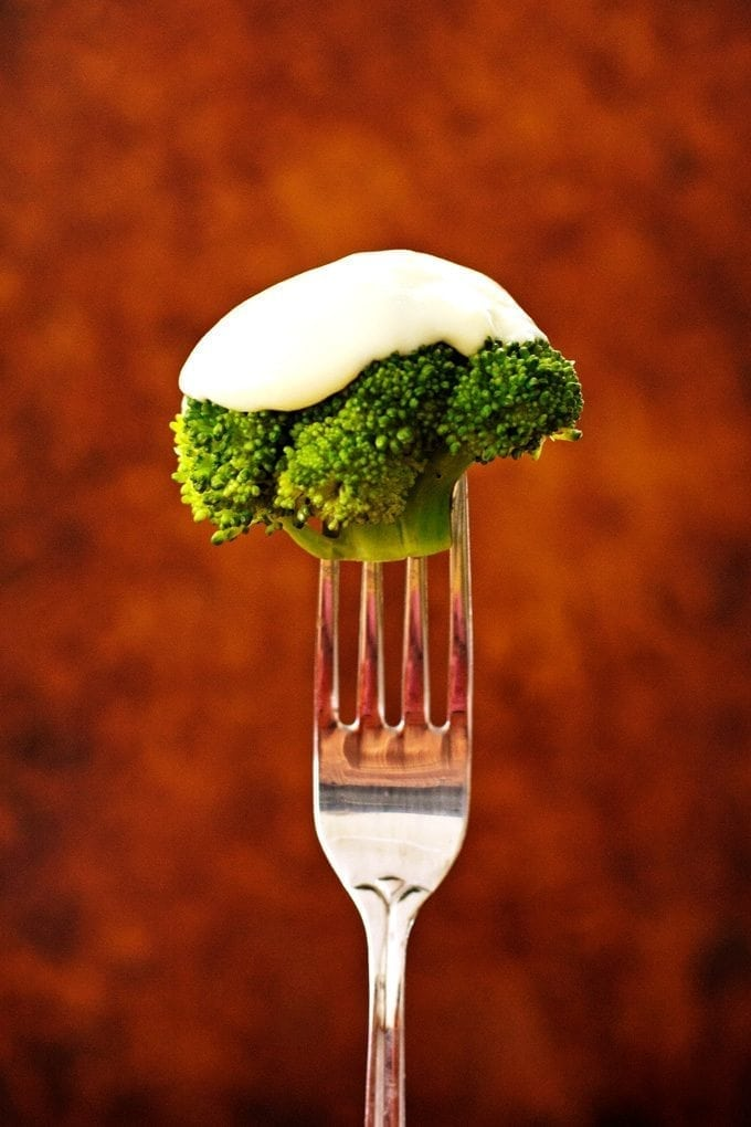 Broccoli covered in cheese sauce on a fork