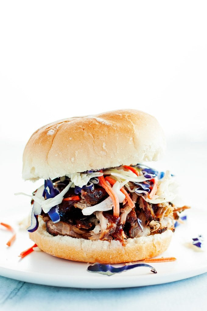 pulled pork sandwich dripping with bbq sauce on a toasted bun topped with colorful purple cabbage and shredded carrots