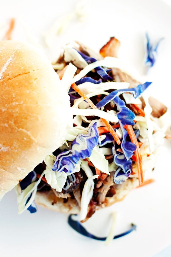 top view of pulled pork sandwich topped with colorful purple cabbage and shredded carrots