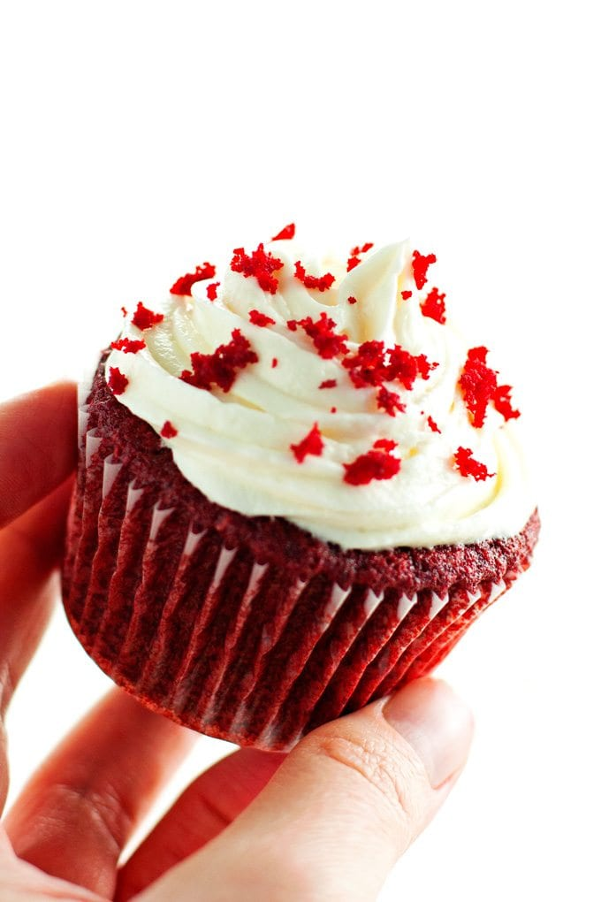 red velvet cupcake being held at a slant to display piped cream cheese frosting