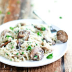 plate and fork full of creamy chicken and mushroom risotto